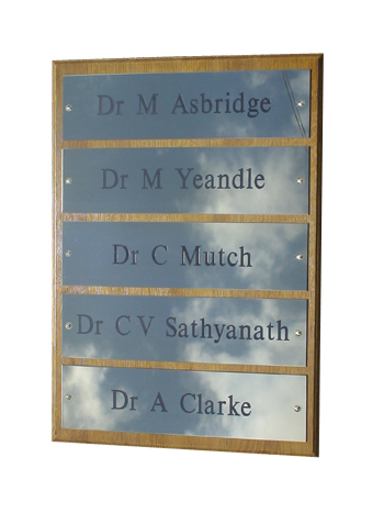 image of a directory board of doctors names engraved and infilled black into polished brass mounted onto a solid oak plinth