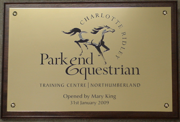 engraved brass plaque with corporate logo colour filled mounted onto solid mahogany plinth dark stain